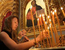 Женщина ставит свечу после поклонения деснице Иоанна Предтечи в Киево-Печерской Лавре. 13 июля
