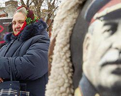 Женщина стоит возле плаката с изображением Сталина во время митинга, посвященного годовщины 89-той годовщине Октябрьской революции. Киев, 7 ноября