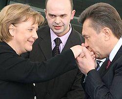 Виктор Янукович демострирует свою галантность во время официальной встречи с канцлером Германии Ангелой Меркель. Берлин, 28 февраля