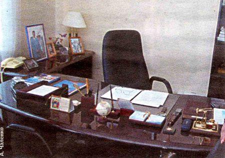 На столе - неперменные атрибуты трудовых будней современного чиновника. Вплоть до мини - скульптурных композиций, тризуба, православного календаря, телефона правительственной связи и очков, дожидающихся премьера.
