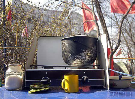 """Полевая кухня с """"окнами"""" на Кабинет министров. В лагерном быту как и всегда все просто: кружка-казан-миска-банка чая и сахара. И походная плита, от которой попахивает пропаном"""