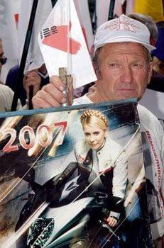 Активіст БЮТ тримає плакат із зображенням лідера БЮТ Юлії Тимошенко, Харків, 4 липня 2007 р.