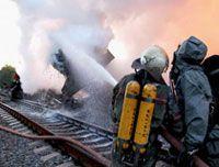 Сотрудники МЧС гасят пожар, возникший в результате падения и возгорания железнодорожных цистерн с жёлтым фосфором
