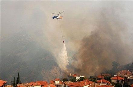 Пожежний гелікоптер над селом Маврики на півдні Греції. (AP Photo)
