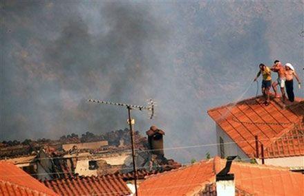 Мешканці с. Маврики на півдні Греції поливають водою дахи своїх будинків. (AP Photo)