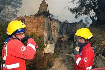 Рятувальники перед згорілим будинком  с. Маврики на півдні Греції. (AP Photo)