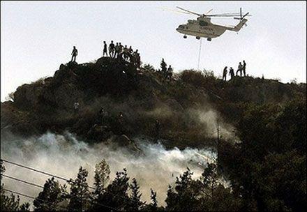 Пожежний вертоліт скидає воду на вогонь біля гори Гіметт, на південний схід від Афін. (Photo AFP)