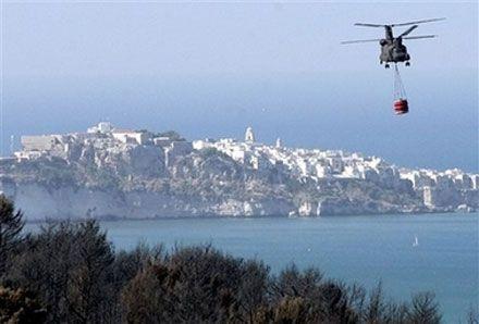 Гелікоптер італійських ВМС, взявши у контейнер воду з Адріатичного моря, прямує до місця пожежі. (AP Photo)