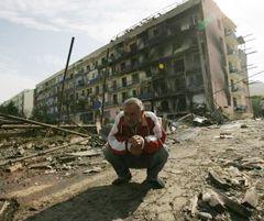 Літній чоловік присів посеред зруйнованої вулиці у місті Горі (Грузія). 11 серпня