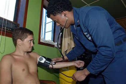 Petty Officer 2nd Class Patrick Satterfield, assigned to the guided-missile destroyer USS Mason, checks the blood pressure of a crew member aboard Motor Vessel Faina
