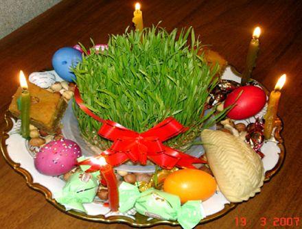 Праздничный стол во время Ноуруза - иранского Нового года, отмечающегося весной. Обязательные атрибуты стола - крашенные яйца, вареники с сыром, свечи, а посредине - миска с проросшим зерном