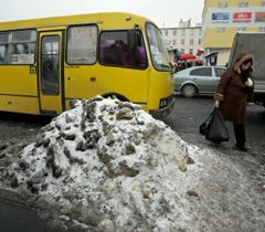Жінка проходить повз кучугуру льоду поряд з територією одного з ринків у Києві. 21 січня
