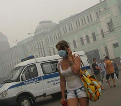 A girl in a respiratory mask at one of the streets of Moscow (Russia). August 6