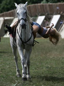 Девушка демонстрирует  трюк, сидя верхом на коне, во время фестиваля каскадеров