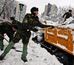 Солдати прибирають сніг на одній з вулиць у Києві. 13 грудня