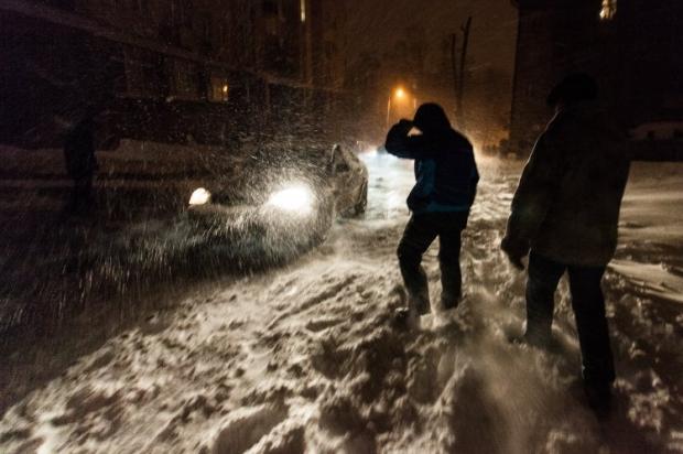 Люди на заснеженной дороге во время снегопада