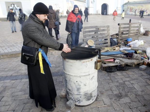На фото - священник греется на Михайловской площади