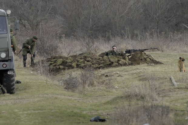 Російські військові риють окоп / REUTERS