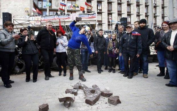 Сепаратисты разбивают герб Украины, который сняли со здания ОГА / facebook.com/EuroMaydan