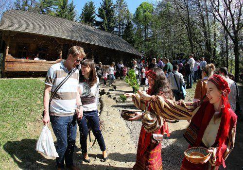 Дівчата в українських національних костюмах зустрічають гостей, окроплюючи їх водою