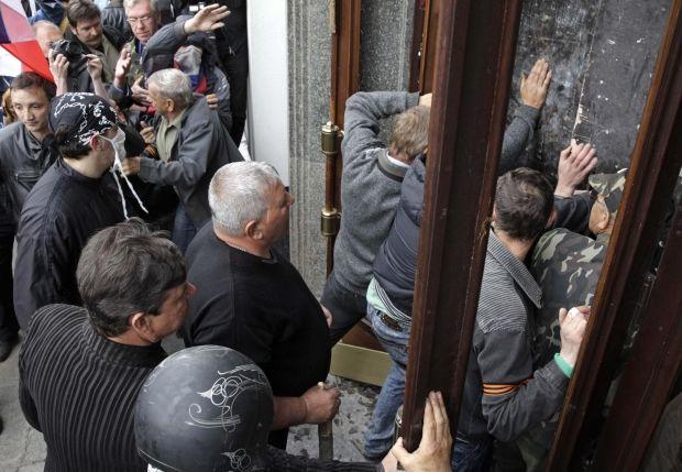 Митингующие выбили окна здания и ворвались вовнутрь / REUTERS