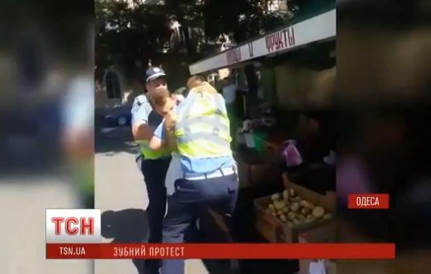 Водій кусає за плече інспектора ДАІ / Скріншот відео