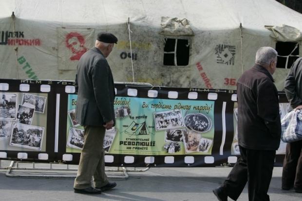 Прохожие рассматривают выставку фотографий и исторических материалов, посвященную 20-й годовщине студенческой голодовки,
