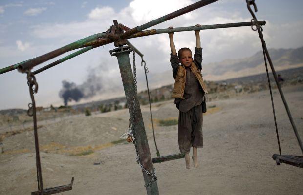 Афганский мальчик играет накарусели на вершине холма в Кабуле, Афганистан 20 июля 2015 года / REUTERS