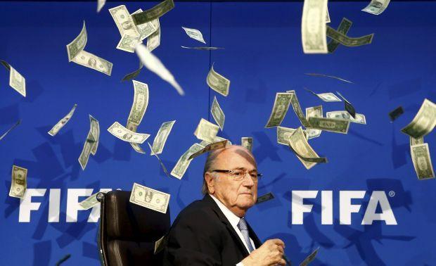 Британский комик известный под именем Ли Нельсон (невидимой) бросает банкноты в президент ФИФА Зеппа Блаттера,после того как он прибыл на пресс-конференцию после внеочередного совещания  Исполнительного комитета в штаб-квартире ФИФА в Цюрихе. Швейцария 20 июля 2015 / REUTERS