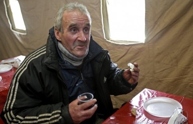 Бездомный пьёт чай в пункте обогрева / Фото: УНИАН