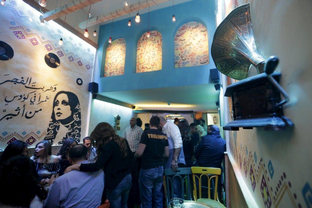 Люди сидят в недавно открывшемся пабе возле портрета ливанской певицы Файруз в Дамаске, 24 марта 2016 года. / REUTERS