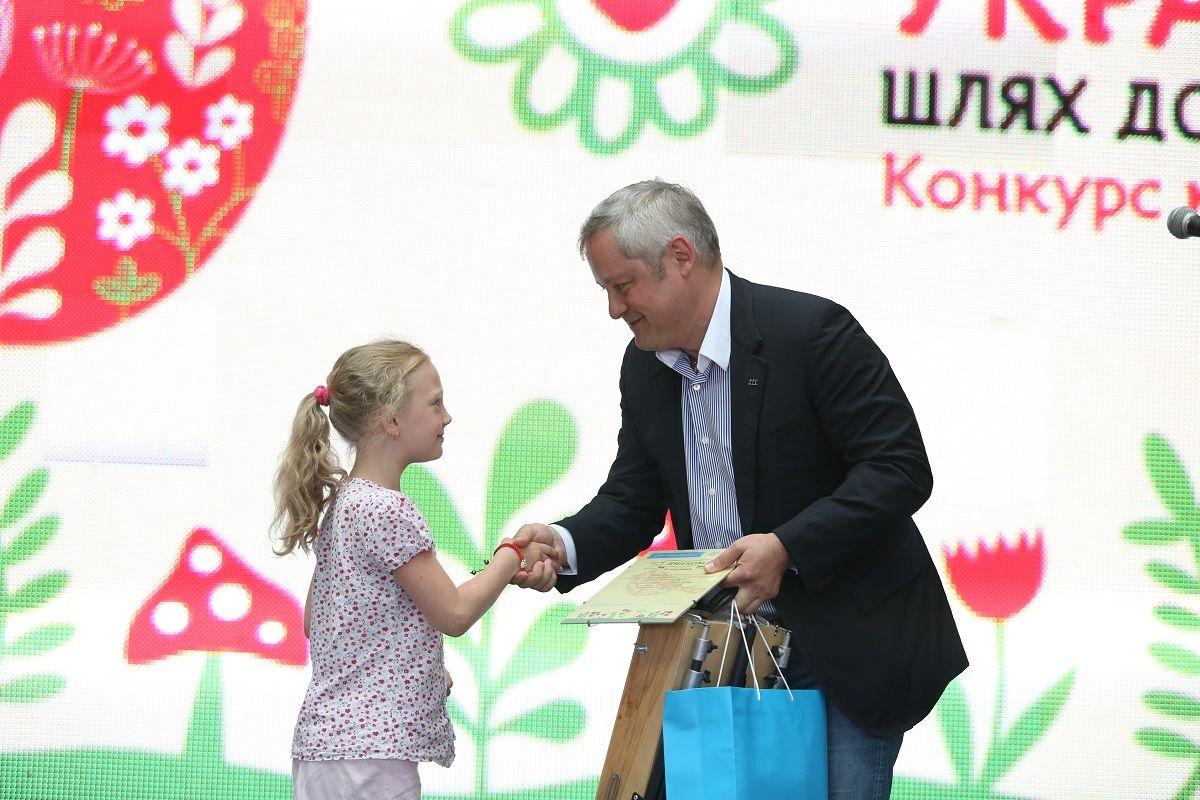 Меценат Ігор Янковський вручає нагороду юній художниці