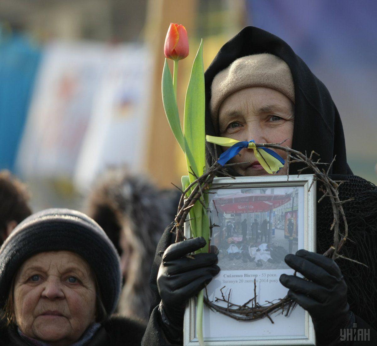 Женщина с портретом погибшего участника Майдана в терновом венке в Киеве, в среду, 26 февраля 2014 / УНИАН