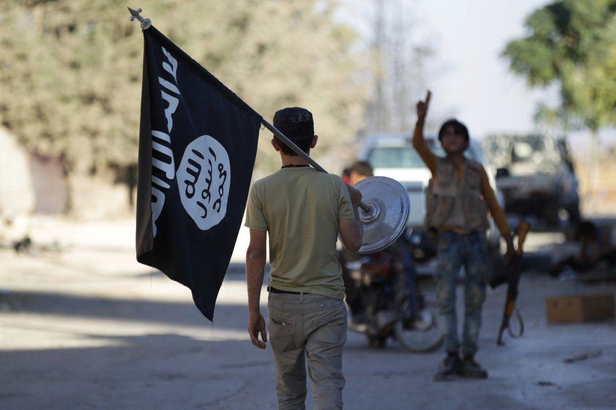 Сирийский повстанец с захваченным флагом