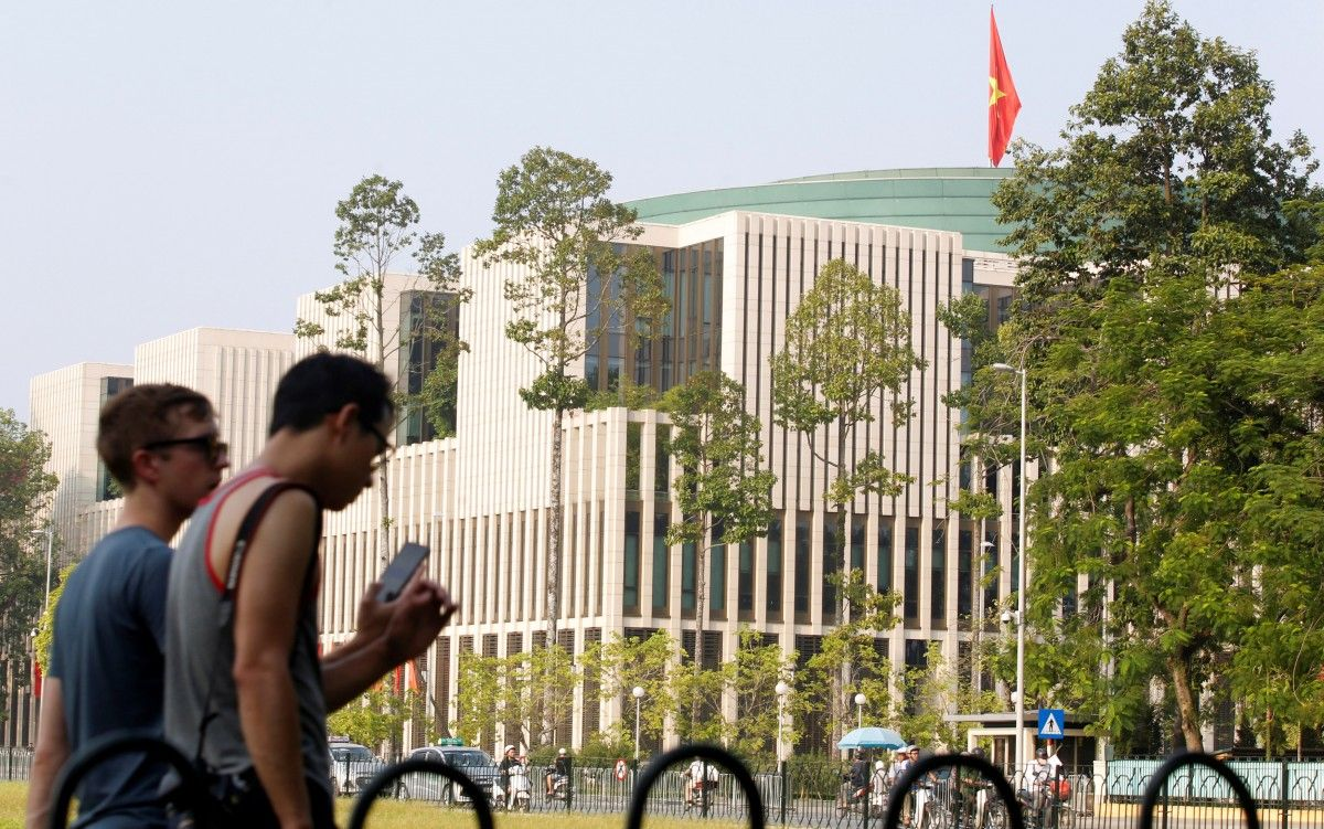Туристы прогуливаются мимо здания Национального Собрания (парламента) в Ханое, Вьетнам / REUTERS