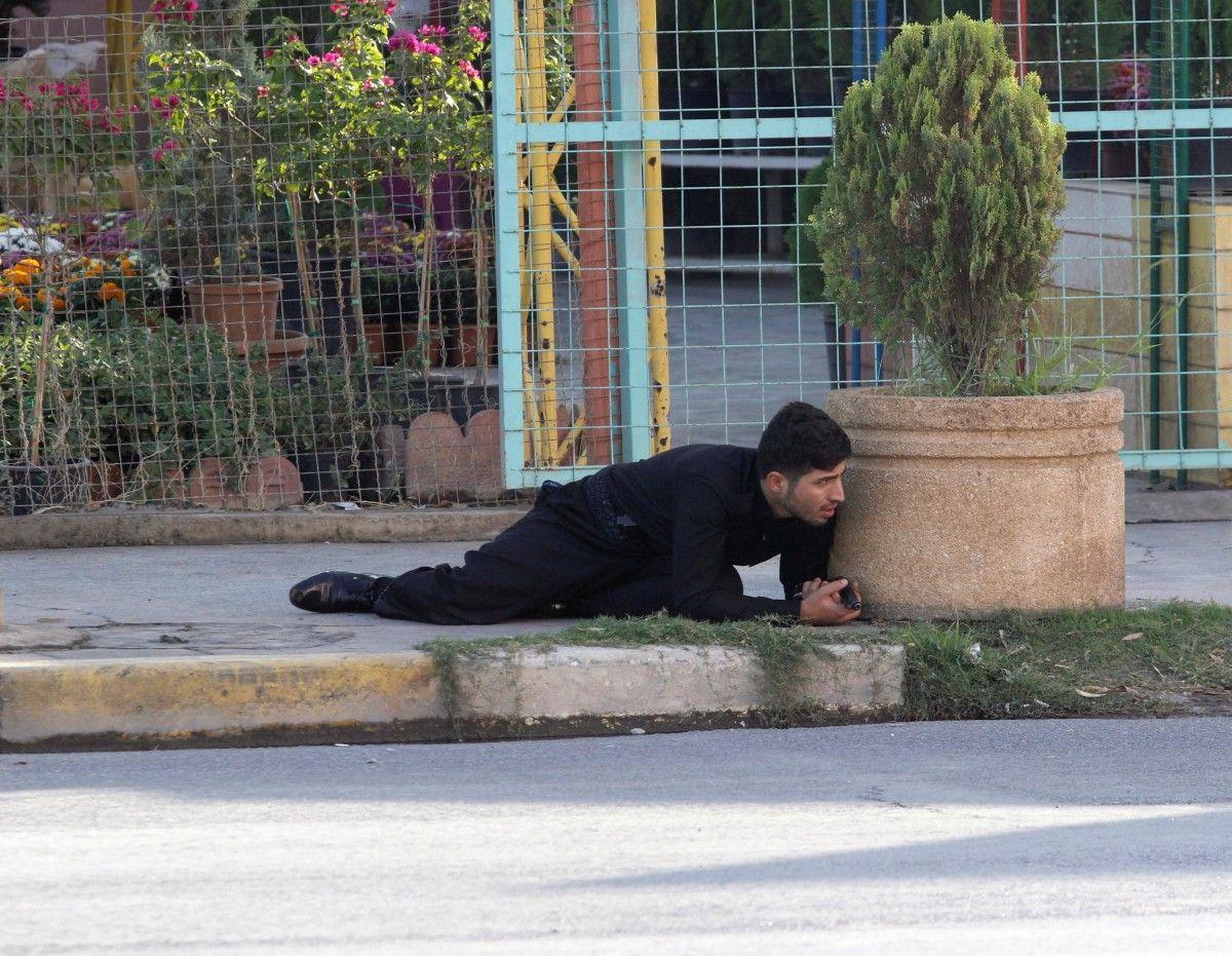 Співробітник курдської служби безпеки ховається на місці нападу ісламських бойовиків в Кіркуку / REUTERS / Співробітник курдської служби безпеки ховається на місці нападу ісламських бойовиків в Кіркуку / REUTERS