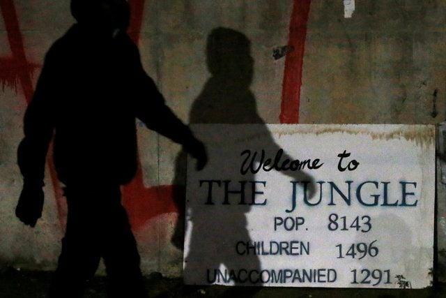Тень мигранта падает на отметку с населением табора в Кале в конце первого дня эвакуации / REUTERS