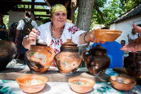 Жінка розписує глиняний посуд