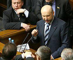 Александр Турчинов выступает в сессионном зале ВР в окружении народных депутатов из Партии регионов, которые заблокировали парламентскую трибуну. Киев, 21 февраля