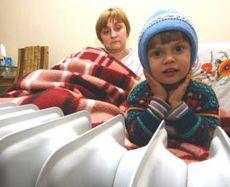 Мать с сыном греются возле масляного электрического радиатора в Евпатории. 10 февраля