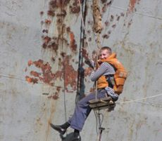 Матрос ЧФ РФ очищає від іржі надводну частину корпусу корабля в Севастополі