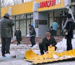 Сотрудники криминалистического центра  работают возле здания поврежденного в результате взрыва в Макеевке. 20 января