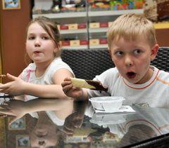 Діти їдять печиво з шоколадом на виставці першого в Україні пересувного музею шоколаду у Харкові