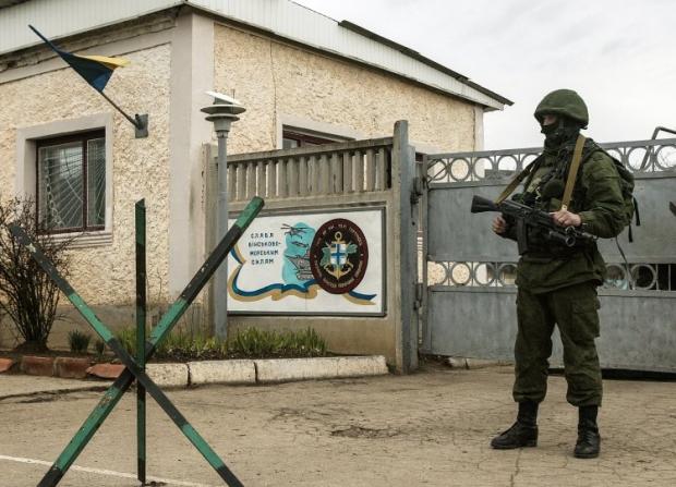 Военнослужащий в камуфляже с оружием блокирует воинскую часть (А 2320) тридцать шестой отдельной бригады береговой обороны ВМС Украины в поселке Перевальное