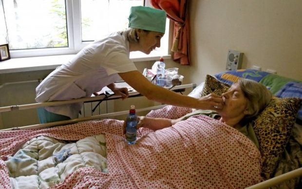Медсестра дає ліки хворій жінці похилого віку / Фото: УНІАН