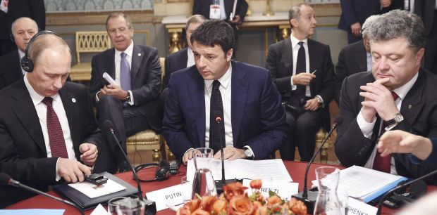 Russian President Vladimir Putin (left) sits with Italian Prime Minister Matteo Renzi (center) and Ukrainian President Petro Poroshenko (right) at talks on the crisis in Ukraine at an EU summit in Milan on Friday  / REUTERS