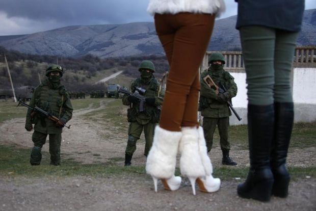 Женщины наблюдают за военными без опознавательных знаков, вероятно российскими, возле украинской военной части под Перевальным, Крым, 5 марта 2014 года / REUTERS