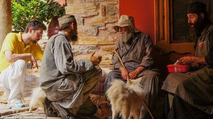 Пожилой монах сидит у входа в монастырь Дохиар.