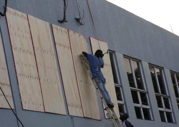 Люди забивають вікна у будівлях в очікуванні урагану / REUTERS