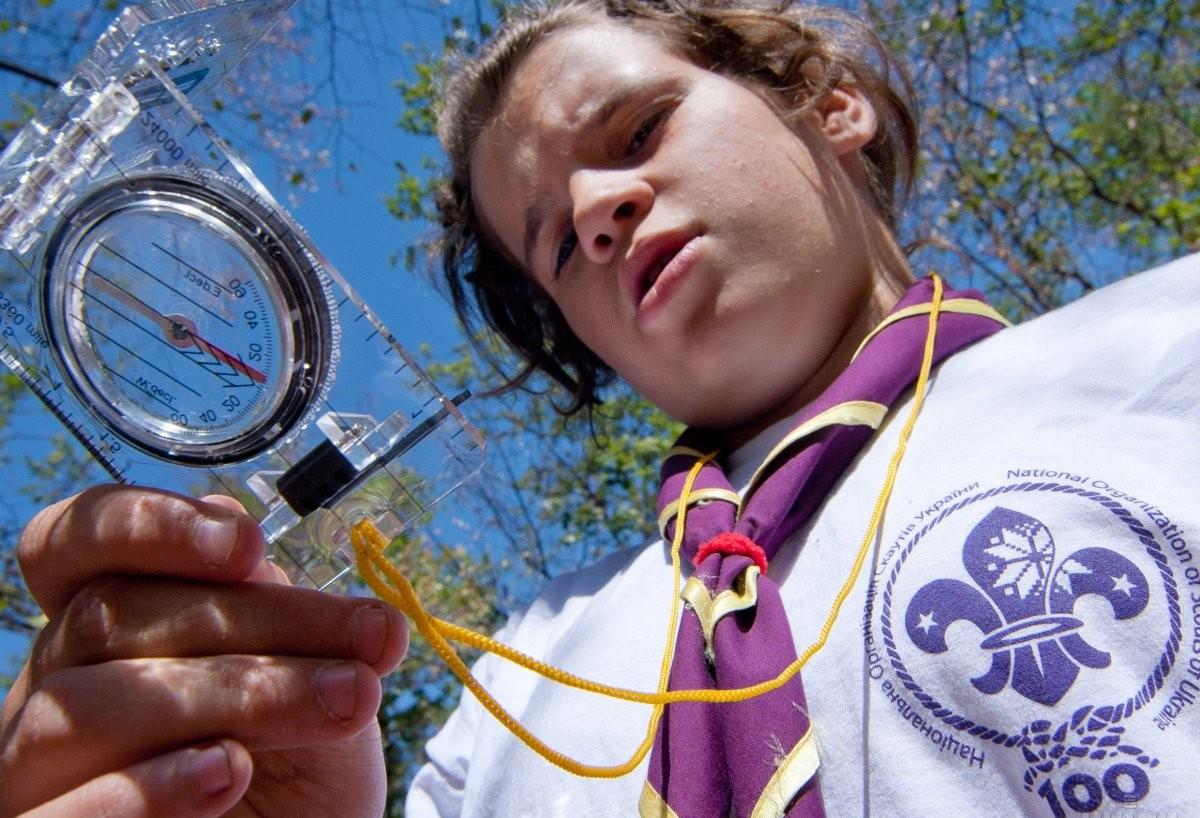 Скаут смотрит на компас в палаточном лагере Всеукраинской молодежной общественной организации